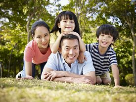 image of japan girl  - happy asian family with two children taking a family photo outdoors in a park - JPG