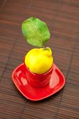 Yellow Quinces With Green Leaves In A Cup On A Bamboo Mat