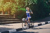 Постер, плакат: Female Cyclist Rides A Racing Bike On Road