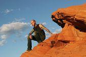 Tattoo man sitting on red rocks