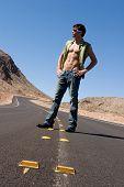 Sexy hombre parado en la carretera vacía