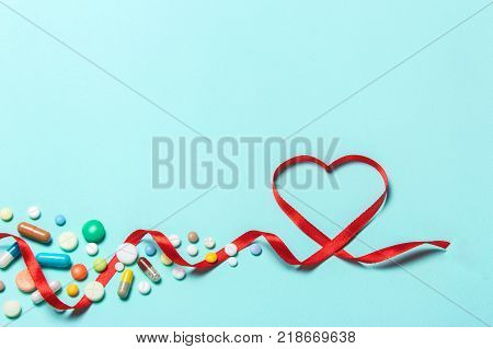 poster of Tablets to treat the heart from a heart attack. Red ribbon in the form of heart and cardiogram