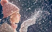 Happy young woman blowing on snow on winter walk in nature. Concept of frost winter season. poster