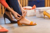 sale, shopping, fashion and people concept - young woman trying sandals at shoe store poster