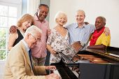 Group Of Seniors Standing By Piano And Singing Together poster