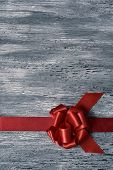 a red satin ribbon gift bow on a rustic gray wooden surface, with a blank space