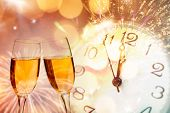 Glasses with champagne against fireworks and clock close to midnight - Celebrating the New Year poster
