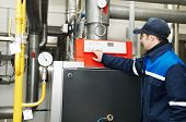 foto of pressure vessel  - maintenance engineer checking technical data of heating system equipment in a boiler house - JPG