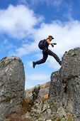 Young Man With Backpack Lands To High Rock