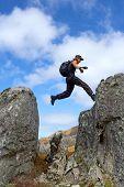 Junger Mann mit Rucksack landet auf hohen Felsens