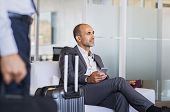Mature businessman expecting airplane at the airport. Thoughtful business man waiting for flight in  poster