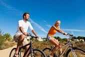 Постер, плакат: Пара в праздники езда на велосипеде под голубым небом в Дюны на пляже