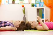 Schoolgirls listening to music via headset on mp3 player together, smiling, lying on floor.?