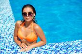 Sexy Young Woman Relaxing In Swimming Pool Water. Girl Enjoying Summer Sun At Pool Edge At Luxury Re poster