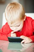 little three year old boy playing with his media player with a puzzled expression  shallow depth of