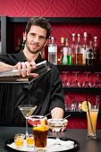 Handsome barman professional at posh bar making cocktail drinks