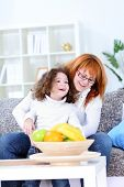 smiling woman tickling her little daughter in living room