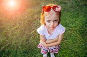 Portrait Of Unhappy Beautiful Little Girl With Blue Eyes In A Red Eyeglasses In Forehead Looking Up  poster