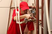 View of a plumber repairing a faucet
