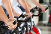 Many hands on spinning bikes in fitness center