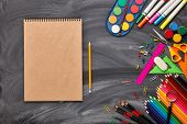 Blank sheet of writing-book and stationery accessories on background of school blackboard. Top view, poster