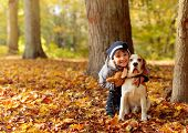 Happy Little Girl With Beagle  In The Autumn Park. Happy Little Girl Hugs Her Pet. poster