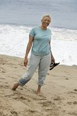 pic of early 60s  - Smiling Woman Walking Barefoot on Beach - JPG