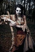 Halloween Theme: Wicked Scary Voodoo Witch With Staff. Portrait Of The Evil Sorceress In Dark Grove. poster