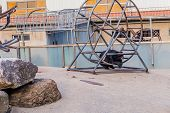Asiatic Black Bear Laying On Metal Exercise Wheel On Hot Afternoon At Local Zoo. poster
