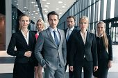 Portrait Of Group Of Young Excited Business People In Formal Wear Standing In Office poster