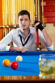 Billiard expertise man posing on blue with alcohol on the rocks glass