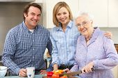 Senior woman and family preparing meal together
