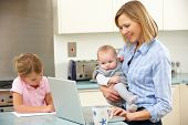 stock photo of mums  - Mother with children using laptop in kitchen - JPG