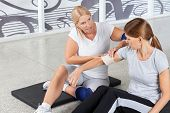 Woman with sports injury gets First Aid from fitness trainer in gym
