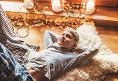 Boy Lying On The Floor And Smiling On Sheepskin In Cozy Home Atmosphere And Dreaming About Christmas poster