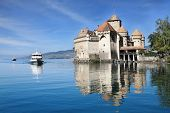 World-wide well-known Ch�¢teau de Chillon on Lake Geneva. The white tourist motor ship floats by a