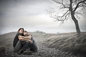 frightened young couple sitting in the middle of nature embrace