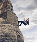 zakenman klimmen op de rotsen