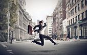 picture of punctuality  - stressed businessman runs through the city - JPG
