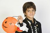 Portrait of a cute Hispanic boy in Halloween outfit with pumpkin bucket