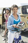 pic of campervan  - Portrait of happy mother and daughter wearing cycling helmet with RV in the background - JPG