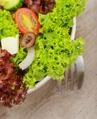 Closeup on traditional greek salad in the plate on wooden table served with fork, green lettuce, fresh vegetables, delicious cuisine, healthy eating concept