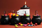 Row Of Halloween Trick Or Treat Witches Cauldrons Full Of Candy On Autumn Brown Background With Blac
