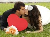 Wedding, beautiful young bride lying together with groom in love on green grass and kissing, park su