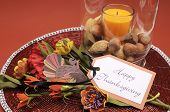 stock photo of centerpiece  - Beautiful Happy Thanksgiving table setting centerpiece with orange candle and nuts in decorative glass hurricane lamp vase and autumn arrangement with turkey decoration - JPG