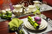 stock photo of christmas meal  - Modern and stylish Christmas dinner table setting including plates glasses and placemats bon bons and Christmas decorations - JPG