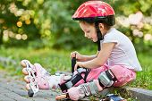 Little girl in protective equipment and rollers fastens knee-pad, sitting on curb of walkway in park