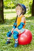 Little boy in protective equipment sits on red ball for jumping on lawn in park