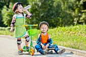 Little boy sits on skateboard next to little girl, who drinks water from plastic bottle, standing wi