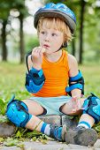 Little boy in protective equipment sits on curb of walkway and eat cracker